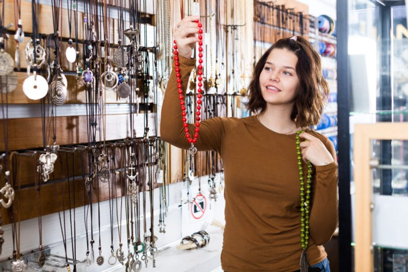 woman choosing between fashion jewelry necklaces