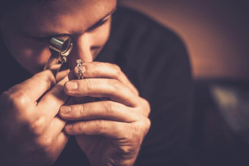 man inspecting jewelry | Sterling Silver Jewelry vs. Pure Silver: What's The Difference?